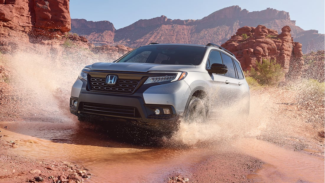 Passenger-side front 3/4 view of 2019 Honda Passport Elite, in Deep Scarlet Pearl, driving on rugged mountain road with accessory roof basket and running boards.