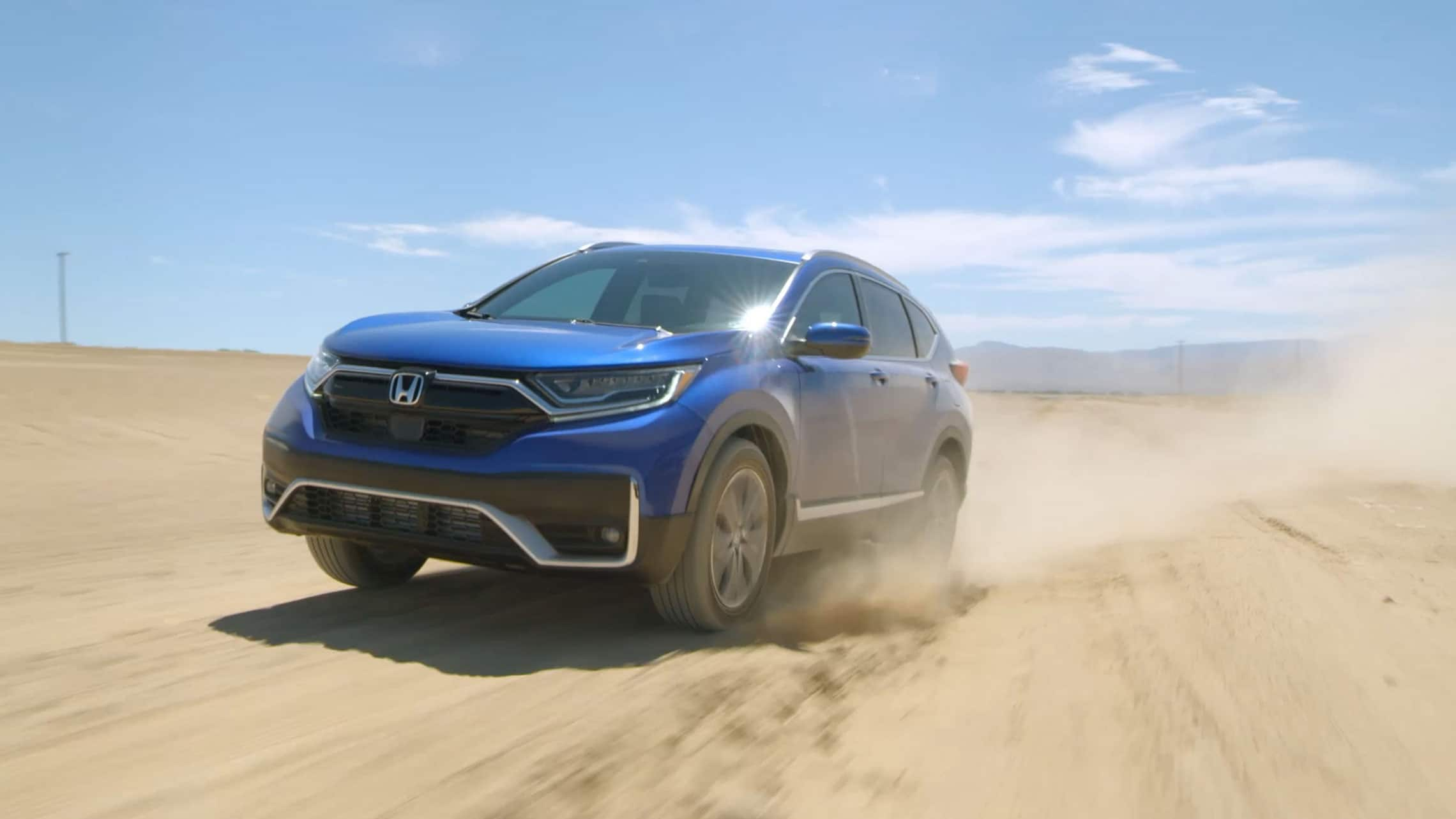 Front driver-side view of the 2020 Honda CR-V AWD Touring in Aegean Blue Metallic, driving on a dirt-road test course.