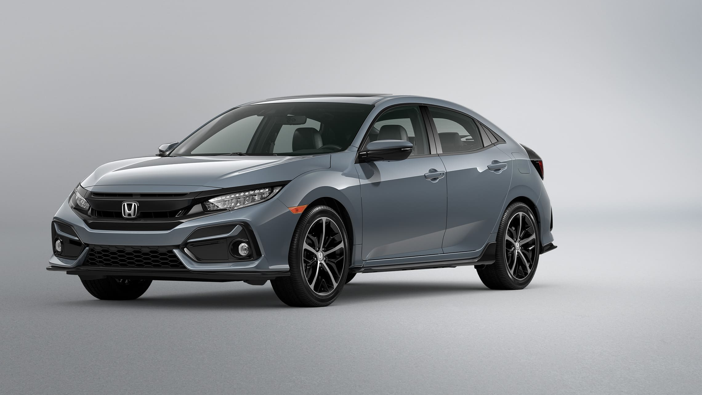 Front 3/4 driver-side view of 2020 Honda Civic Sport Touring Hatchback in Sonic Gray Pearl.