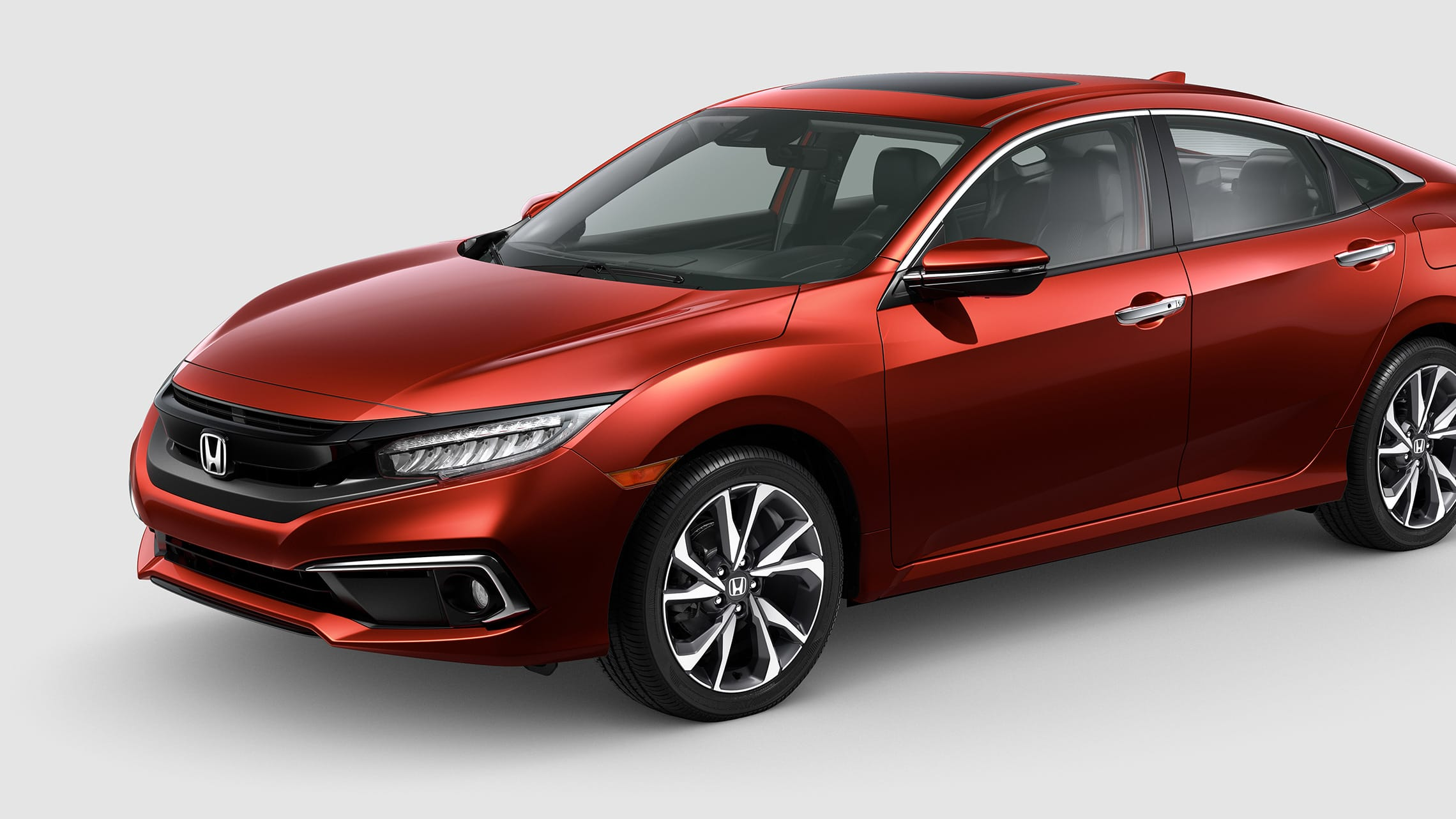 Front driver-side view of the 2021 Honda Civic Touring Sedan in Molten Lava Pearl.