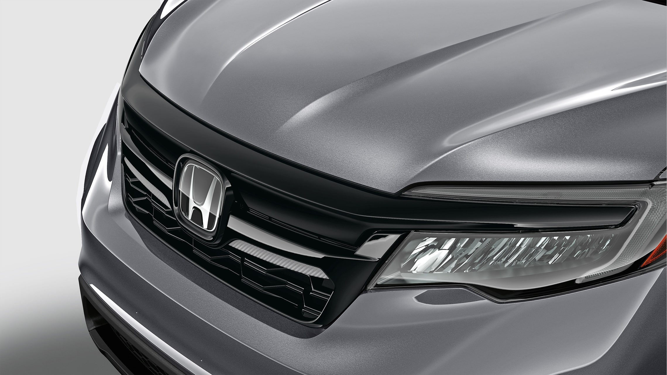 Front grille carbon inserts detail in black on 2021 Honda Pilot in Modern Steel Metallic.
