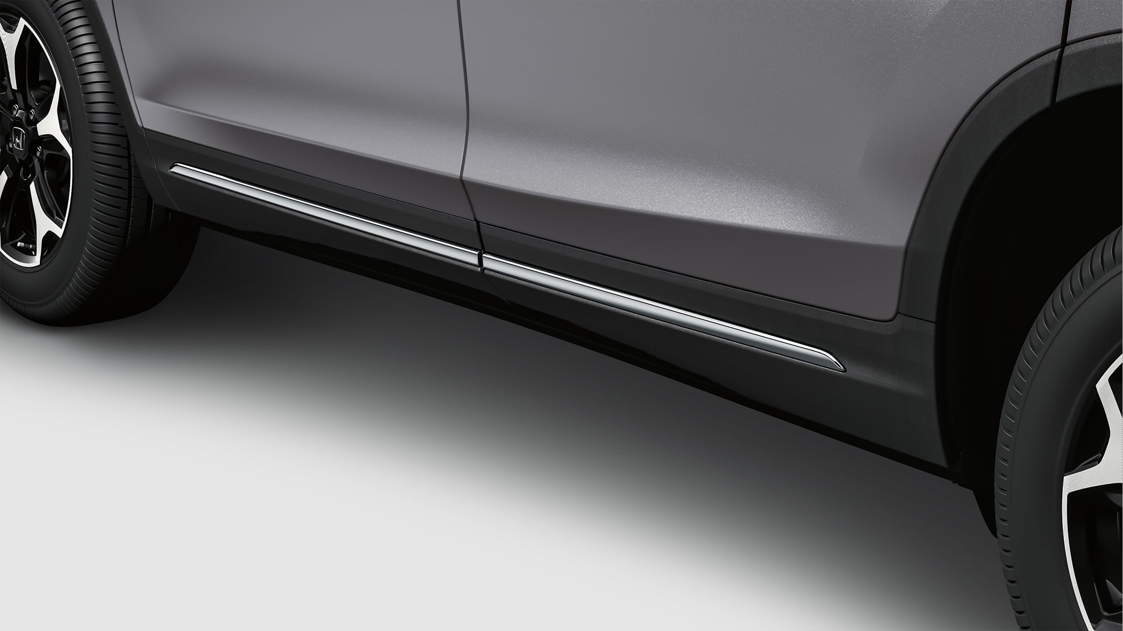 Close-up side view of lower door trim detail on 2021 Honda Pilot in Modern Steel Metallic.