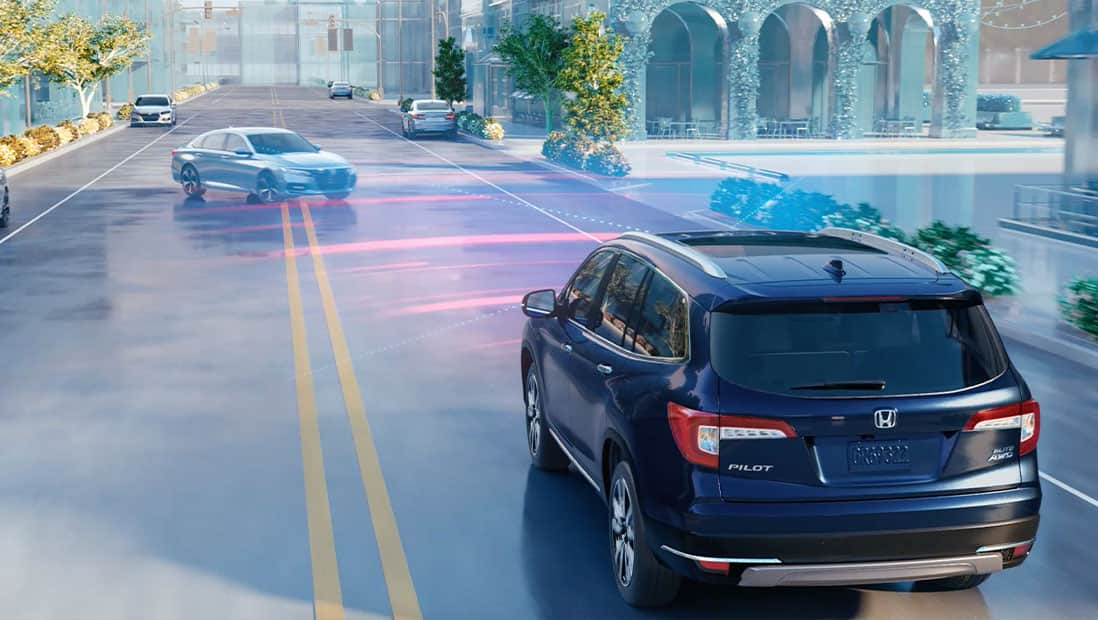 Rear 7/8 driver-side view of 2021 Honda Pilot Elite in Modern Steel Metallic displaying Collision Mitigation Braking System™ technology.